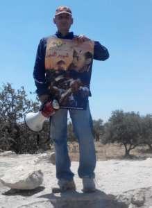 Palestyńczyk z plakatem upamiętniającym śmierć Muhammada Abu Chidajra