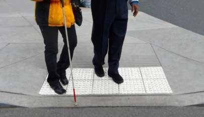 Osoba niewidoma używająca tzw. białej laski. Źródło: Wikimedia.