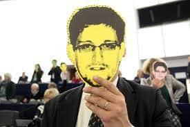 Fotografia człowieka zasłaniającego twarz maską z podobizną Edwarda Snowdena.
