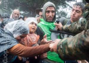 Macedonian border police help refugees and migrants to pass from the northern Greek village of Idomeni to southern Macedonia, Sept. 10, 2015. Thousands of people braved torrential downpours to cross Greece's northern border with Macedonia early Thursday.