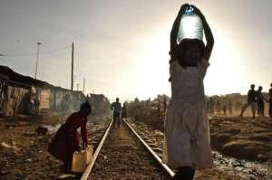 Młoda kobieta niesie butelkę wody w slumsach w Nairobi, w Kenii/flickr.com