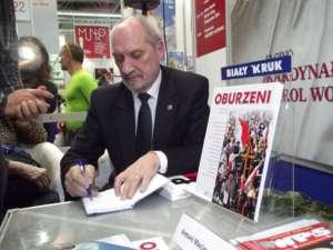 Antoni Macierewicz podpisuje książkę pod znaczącym tytułem na Targach Książki w Krakowie, fot. wikimedia commons