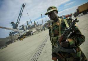 SOMALIA, Mogadishu: In a photograph released by the African Union-United Nations Information Support Team 06 August 2012, a soldier of the African Union Mission in Somalia (AMISOM) keeps guard inside the seaport of the Somali capital Mogadishu. August 06 is the one-year anniversary marking the date that Al-Qaeda-affiliated extremist group Al Shabaab withdrew from fixed positions in Mogadishu after having steadily lost territory to forces of the Transitional Federal Government (TFG) backed by troops from the African Union Mission in Somalia (AMISOM), ending their draconian stranglehold on the capital and its population. In the last 12 months, residents of Mogadishu have enjoyed the longest period of relative peace in their city for 20 years, with re-building and re-generation work taking place all over the city and businesses and a semblance of normal daily life returning to the now busy streets of the war-shattered Horn of Africa capital. AU-UN IST PHOTO / STUART PRICE.